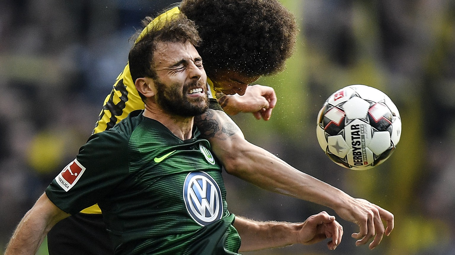 Wolfsburg's Admir Mehmedi, left, and Dortmund's Axel Witsel, right, challenge for the ball during the German Bundesliga soccer match between Borussia Dortmund and VfL Wolfsburg in Dortmund, Germany, Saturday, March 30, 2019. (AP Photo/Martin Meissner)