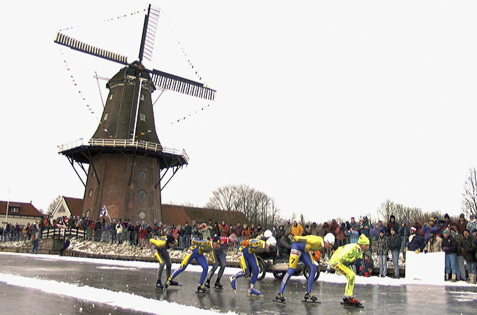 FILE - In this Jan. 4, 1997, file photo, skaters pass a windmill as some 16,000 people participate in the historic 200km skating spectacle the 'Elfstedentocht' (eleven-cities-course) in Birdaard, province of Friesland, northern Netherlands. There is nothing more mythical in Dutch sports than an age-old 11-city race skating across lakes and canals in bone-numbing cold from dawn to dusk. No wonder the Netherlands is the greatest speedskating nation in the world. And with Sven Kramer and Ireen Wust leading the way on big oval in Sochi they are bent on proving it again.  (AP Photo/Dimitri Georganas, File)