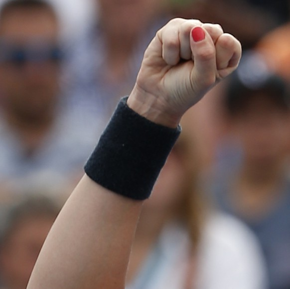 Timea Bacsinszky of Switzerland celebrates after defeating Jelena Jankovic of Serbia in their first round match at the Australian Open tennis championship in Melbourne, Australia, Tuesday, Jan. 20, 2015. (AP Photo/Vincent Thian )