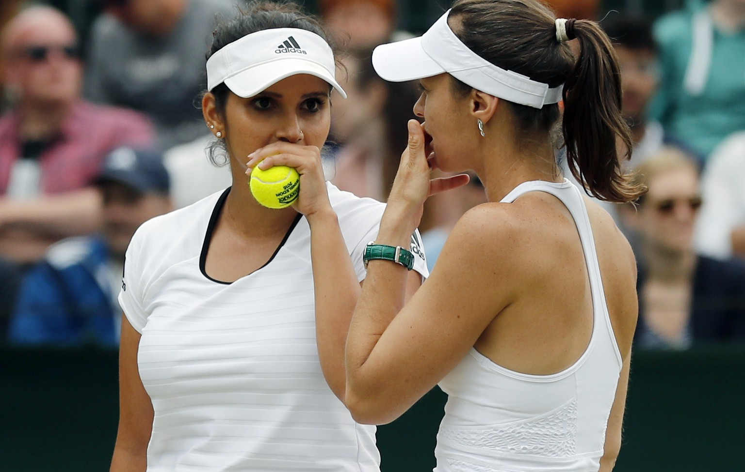 Sania Mirza of India, left, speaks with her partner Martina Hingis of Switzerland during their women's doubles match against Christina McHale of the U.S and Jelena Ostapenko of Latvia on day eight of the Wimbledon Tennis Championships in London, Monday, July 4, 2016. (AP Photo/Ben Curtis)
