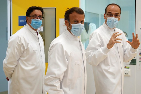 epa08487818 French President Emmanuel Macron, Thomas Triomphe, Executive Vice President of Sanofi Pasteur, and Paul Hudson, Chief Executive Officer of Sanofi, wearing protective face masks, visit an industrial development laboratory at the French drugmaker's vaccine unit Sanofi Pasteur plant in Marcy-l'Etoile, near Lyon, France, June 16, 2020.  EPA/GONZALO FUENTES / POOL  MAXPPP OUT