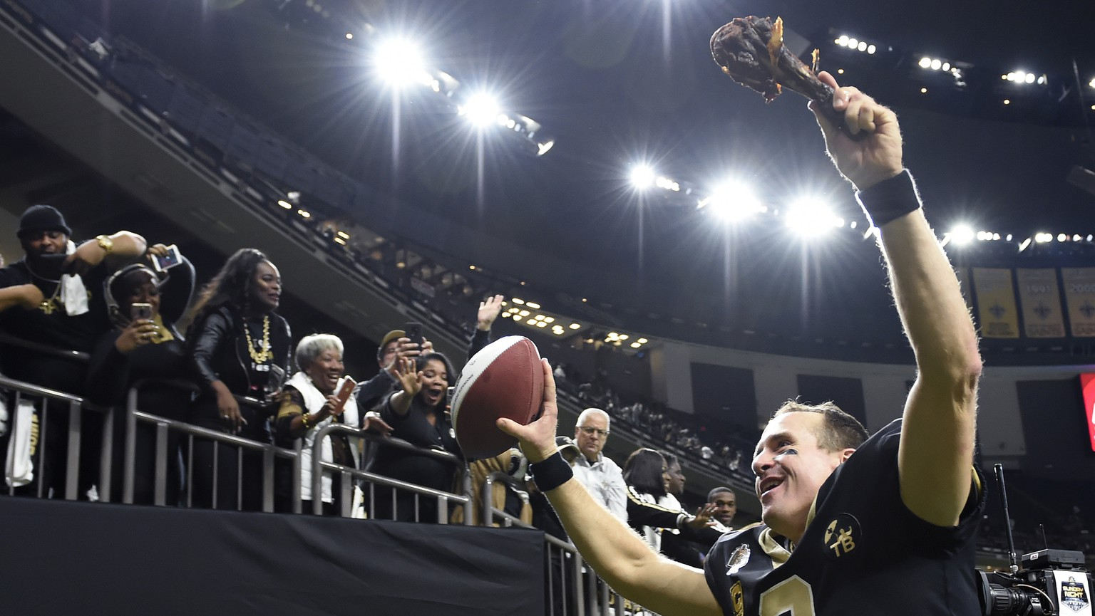 New Orleans Saints quarterback Drew Brees (9) responds to the fans with a turkey drumstick as he runs off the field Thanksgiving night after an NFL football game against the Atlanta Falcons in New Orleans, Thursday, Nov. 22, 2018. The Saints won 31-17. (AP Photo/Bill Feig)