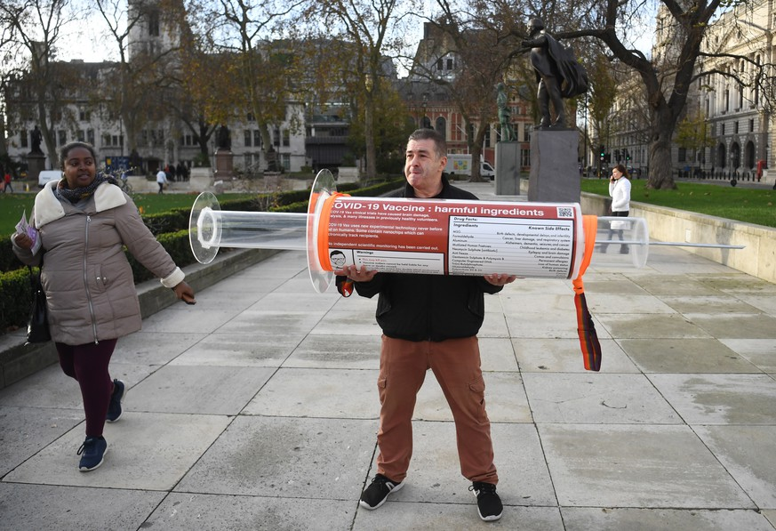 epa08839320 A man holds an oversized syringe after protesting against Covid-19 vaccination, outside the headquarters of the Bill and Melinda Gates Foundation in London, Britain, 24 November 2020. Vaccine trials from a number of pharmaceutical companies are proving successful, giving hope at ending restrictions due to the ongoing coronavirus pandemic.  EPA/NEIL HALL