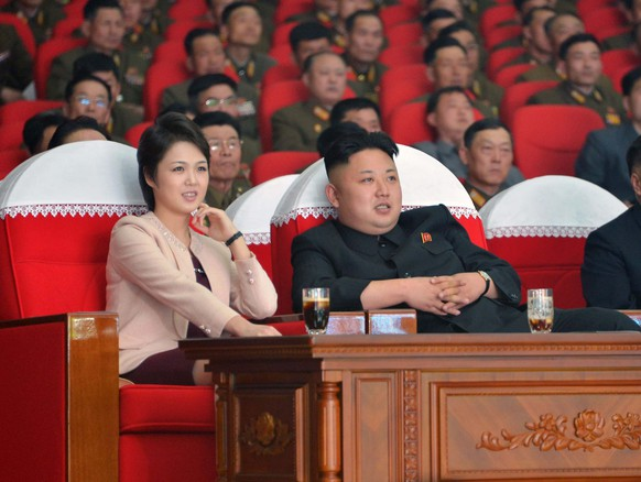 epa04138357 A picture released by the North Korean Central News Agency (KCNA) on 24 March 2014 shows North Korean leader Kim Jong-un (R) attending a performance by the Moranbong Band in Pyongyang, North Korea, 22 March 2014. At left is his wife, Ri Sol-ju.  EPA/KCNA SOUTH KOREA OUT