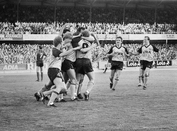 Die Berner Spieler jubeln im Spiel gegen Xamax am 24. Mai 1986 in Neuenburg. Von links nach rechts, Martin Weber, Lars Lunde und die dazu eilenden Roland Schoenenberger und Juerg Wittwer. YB sichert sich mit einem 4:1 Sieg die Meisterschaft vorzeitig. (KEYSTONE/Str)
