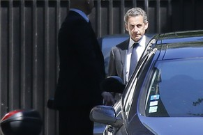 Former French President Nicolas Sarkozy (R) leaves his residence in Paris, July 2, 2014. Former French President Nicolas Sarkozy was placed under formal investigation on Wednesday on suspicions he tried to use his influence to thwart an investigation of his 2007 election campaign, the prosecutor's office said.   REUTERS/Gonzalo Fuentes (FRANCE - Tags: POLITICS CRIME LAW)