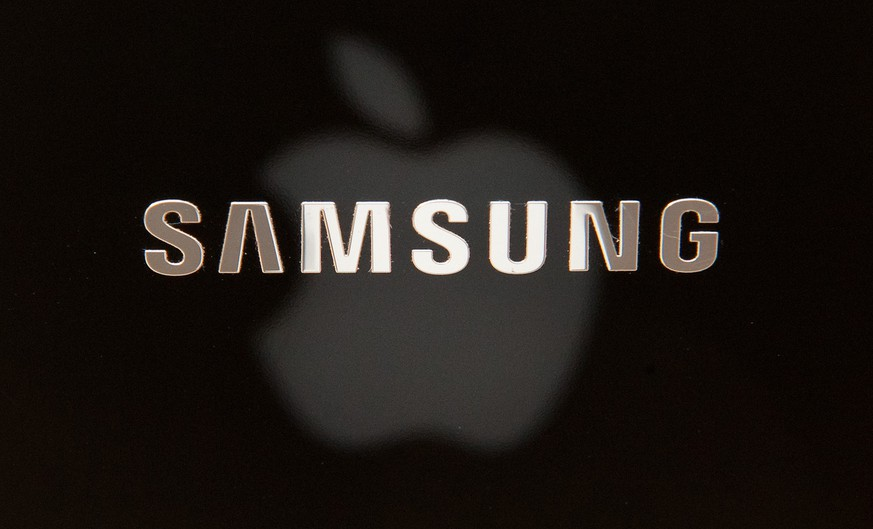 FILE - This photo illustration made July 24, 2012 shows the Apple Inc. logo reflected on a Samsung notebook computer in Duesseldorf, Germany. After a year of scorched-earth litigation, a jury in San Jose, Calif., decided Friday, Aug. 24, 2012 that Samsung ripped off the innovative technology used by Apple to create its revolutionary iPhone and iPad. The jury ordered Samsung to pay Apple $1.05 billion. An appeal is expected. (AP Photo/dapd, Patrick Sinkel, File)