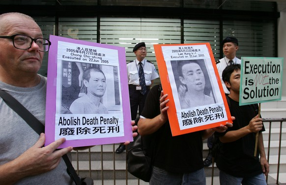 A group of members from various committees for the Abolition of the Death Penalty carry placards, featuring Hong Kong drug offenders who had been executed in mainland China, demonstrate in front of the China Liaison Office in Hong Kong on Thursday July 14, 2005. Protesters urge the Chinese government abolition of the dealth penalty. (AP Photo/Kin Cheung)