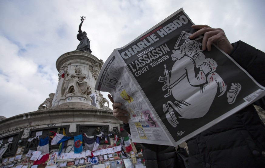 epa05089591 A man reads a copy of French satirical newspaper Charlie Hebdo's one-year anniversary edition of last year's January attacks near the makeshift memorial site on Place de la Republique in Paris, France, 06 January 2016.  France this week commemorates the victims of last year's Islamist militant attacks on satirical weekly Charlie Hebdo and a Jewish supermarket with eulogies, memorial plaques and another cartoon lampooning religion. The cover of the special issue No. 1224 of the French satirical weekly Charlie Hebdo with a cartoon of a bearded god carrying a kalashnikov reading '1 an apres. L'assassin court toujours' (lit: One year later.The murderer is still on the run).  EPA/IAN LANGSDON