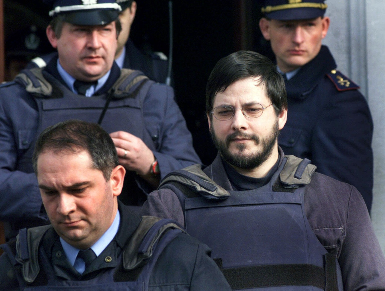 FILE - In this Monday, March 20, 2000 file photo, Marc Dutroux, right, is led out the courthouse of Neufchateau, Belgium, 180 kilometers (130 miles) east of Brussels. Marc Dutroux, a pedophile and child-killer who became one of Belgium's most notorious criminals, is asking a sentencing court on Monday, Feb. 4, 2013 to release him from prison and monitor him with an electronic ankle bracelet. Dutroux, who is now 56, is serving a life term for kidnapping, torturing and abusing six girls in 1995 and 1996, and murdering four of them. He has been in prison for 16 years. His former wife, Michelle Martin, 53, who let two girls starve to death in the cellar while her husband was in jail for theft was approved for early release in July. She now lives in a convent. The court is not expected to rule on Dutroux's request for freedom until Feb 18. Prison officials and prosecutors have recommended against his release. (AP Photo/Yves Logghe, File)