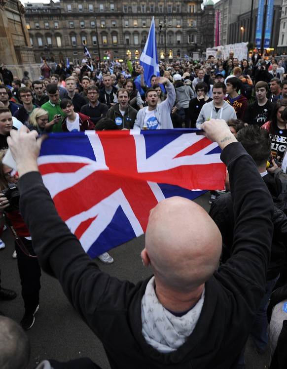 Pro-Union supporters clash with pro-Independence supporters in George Square, Glasgow, Scotland, on September 18, 2014, during a referendum on Scottish independence. Scotland began voting Thursday on whether to become independent from Britain in a referendum which has electrified the nation, dominating debate in homes and pubs from Edinburgh to the Highlands. AFP PHOTO / ANDY BUCHANAN