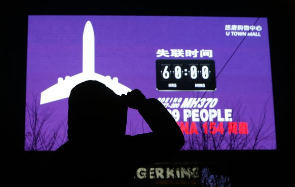 """A woman looks on in front of a giant screen showing the hours since Malaysia Airlines flight MH370 went missing and the number of passengers onboard, including 154 Chinese people, at a shopping mall, in Beijing March 10, 2014. The disappearance of a Malaysian airliner about an hour into a flight to Beijing is an """"unprecedented mystery"""", the civil aviation chief said on Monday, as a massive air and sea search now in its third day failed to find any trace of the plane or 239 people on board. REUTERS/Jason Lee (CHINA - Tags: DISASTER TRANSPORT)"""