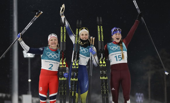 Gold medal winner Stina Nilsson, of Sweden, is flanked by silver medal winner Maiken Caspersen Falla, of Norway, left, and bronze medal winner Yulia Belorukova, of the team from Russia, after the women's cross-country skiing sprint classic at the 2018 Winter Olympics in Pyeongchang, South Korea, Tuesday, Feb. 13, 2018. (AP Photo/Kirsty Wigglesworth)