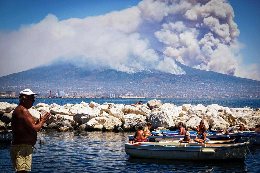 epa06081178 A general view over the city as smoke billows from fires around Mount Vesuvius volcano in Naples, Italy, 11 July 2017. Fires continue to rage after they broke out on 05 July around the active volcano.  EPA/CESARE ABBATE