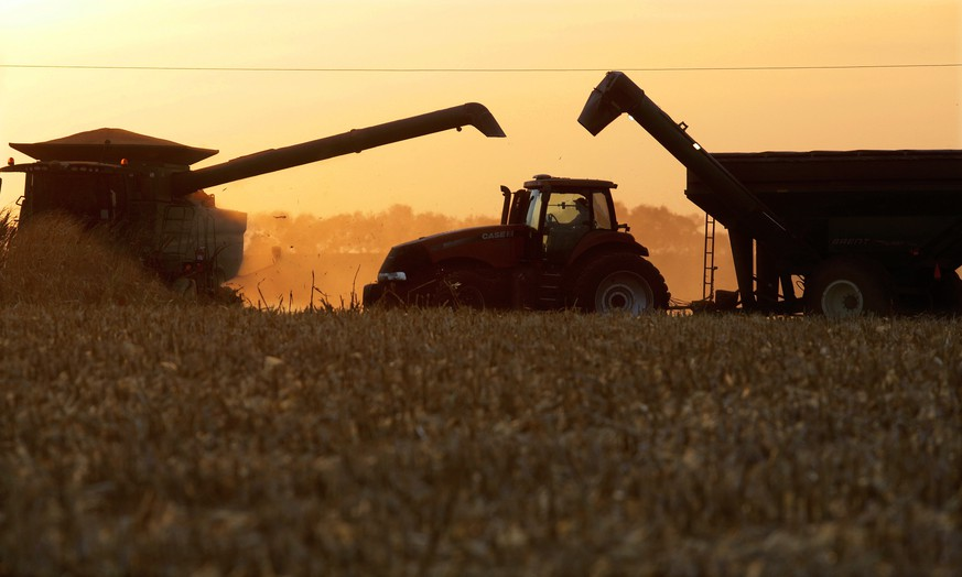 Central Illinois farmers continue to harvest their corn crops as the sun sets Monday, Oct. 17, 2016, in Berlin, Ill. The corn and soybean harvests are well underway in the Midwest and helped by excellent weather conditions. (AP Photo/Seth Perlman)