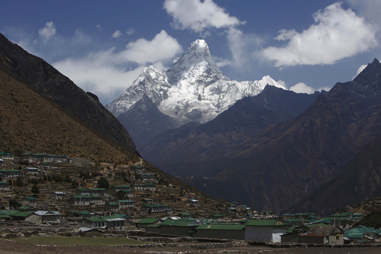 Mount Ama Dablam, which stands approximately 6800 meters above sea level, is seen behind Khumjung Village in Solukhumbu District April 30, 2014. More than 4,000 climbers have reached the summit of Everest, the world's highest peak, since it was first scaled by Sir Edmund Hillary and Tenzing Norgay Sherpa in 1953. In April, an avalanche killed 16 Nepali Sherpa guides who were fixing ropes and ferrying supplies for their foreign clients to climb the 8,850-metre (29,035-foot) peak. The accident - the deadliest in the history of Mount Everest - triggered a dispute between sherpa guides who wanted a climbing ban in honour of their colleagues and the Nepali government that refused to close the mountain. The sherpas staged a boycott, forcing hundreds of foreign climbers to call off their bids to climb Everest.  Picture taken April 30, 2014. REUTERS/Navesh Chitrakar (NEPAL - Tags: ENVIRONMENT SOCIETY BUSINESS EMPLOYMENT TRAVEL)