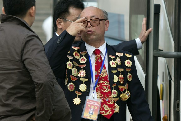 A man covered in medals leave a May Day event to celebrate China's model workers outside the Great Hall of the People in Beijing, Friday, May 1, 2015. Millions of Chinese are taking advantage of the May Day holidays to visit popular tourist sites. (AP Photo/Ng Han Guan)