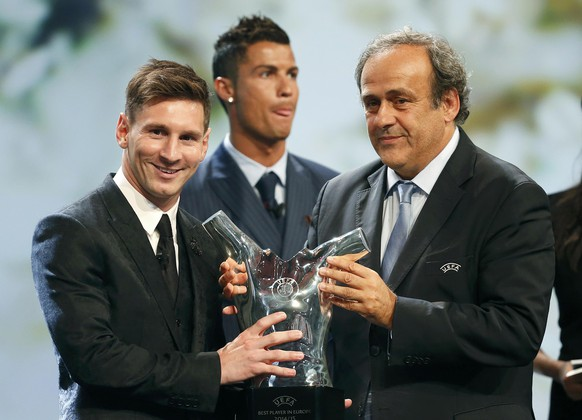 Barcelona's Lionel Messi (L) receives from UEFA President Michel Platini the Best Player UEFA 2015 Award during the draw ceremony for the 2015/2016 Champions League Cup soccer competition at Monaco's Grimaldi Forum while Cristiano Ronaldo (C) looks on in Monte Carlo August 27, 2015.  REUTERS/Eric Gaillard
