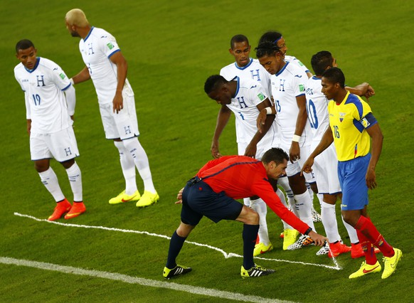 Referee Benjamin Williams of Australia marks the ground with vanishing spray during the match 2014 World Cup Group E soccer match between Honduras and  Ecuador at the Baixada arena in Curitiba June 20, 2014. REUTERS/Amr Abdallah Dalsh (BRAZIL  - Tags: SOCCER SPORT WORLD CUP)