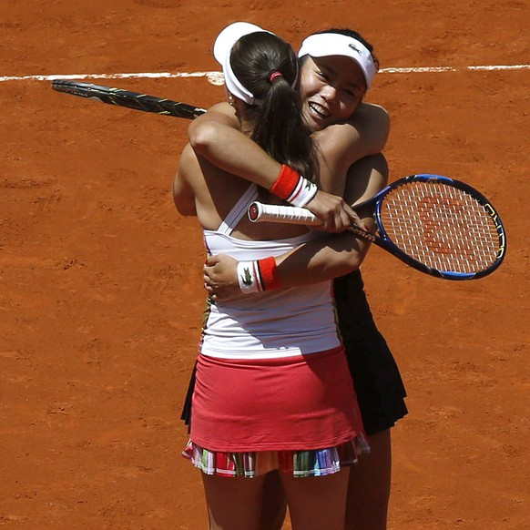 epa05961362 Switzerland's Martina Hingis (L) and Yung-Jan Chan from Taiwan (R) celebrate their victory in the Women's doubles final against Czech Andrea Hlavackova and Hungarian Timea Babos at the Mutua Madrid Open tennis tournament in Madrid, Spain, 13 May 2017.  EPA/SERGIO BARRENECHEA