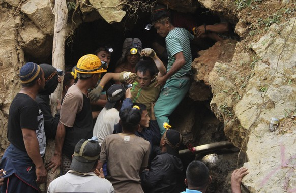 FILE - In this Feb. 27, 2019, file photo, rescuers carry a survivor from inside a collapsed mine in Bolaang Mongondow, North Sulawesi, Indonesia. Indonesian authorities say they're not certain how many people were buried in the collapse of a remote gold mine nearly a week ago but that the number could be as high as 100. (AP Photo/Harry Tri Atmojo, File)