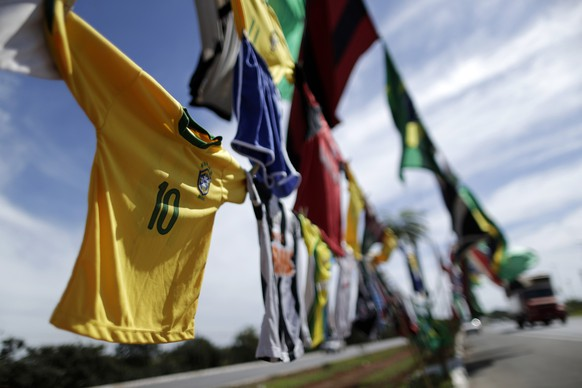 Shirts and flags of the Brazilian national football team are displayed for sale on a street in Brasilia, May 3, 2014. REUTERS/Ueslei Marcelino (BRAZIL - Tags: SPORT SOCCER WORLD CUP)
