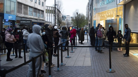 Early morning shoppers in Birmingham, England, Monday April 12, 2021. Millions of people in Britain will get their first chance in months for haircuts, casual shopping and restaurant meals on Monday, as the government takes the next step on its lockdown-lifting road map. (Jacob King/PA via AP)