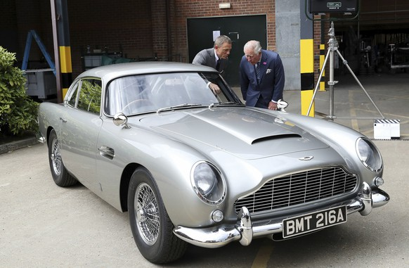 Britain's Prince Charles talks with actor Daniel Craig left as they view the Aston Martin DB5 Bond car during a visit to the set of the 25th James Bond film at Pinewood Studios in Iver Heath southern England Thursday