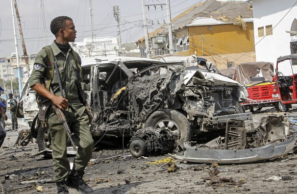 A member of the security forces walks past wreckage at the scene of a bombing in Mogadishu, Somalia Saturday, Feb. 13, 2021. Police say a suicide bomber died and a number of civilians were wounded when a vehicle exploded near a checkpoint outside the presidential palace in Somalia's capital, Mogadishu. (AP Photo/Farah Abdi Warsameh)