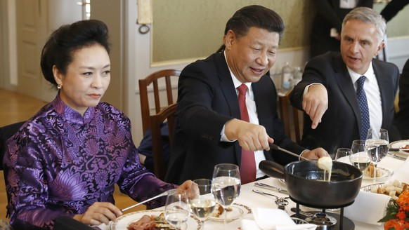 China's President Xi Jinping, center, Xi's wife Peng Liyuan, left, and Swiss Foreign Minister Didier Burkhalter eat Swiss cheese fondue during lunch during Xi's two days state visit to Switzerland in Bern, Switzerland, Monday, Jan. 16, 2017.  (Peter Klaunzer/Pool Photo via AP)