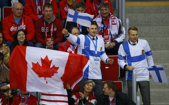 Fans of Team Canada and of Finland wait for the start of their men's preliminary round ice hockey game at the 2014 Sochi Winter Olympics, February 16, 2014.  REUTERS/Brian Snyder (RUSSIA  - Tags: OLYMPICS SPORT ICE HOCKEY)