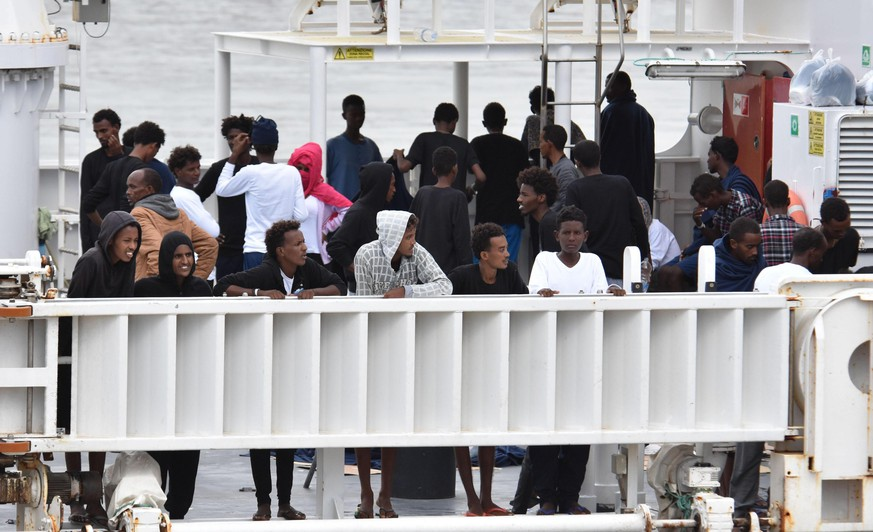 epa06961964 Migrants are seen onboard the Italian Coast Guard ship Diciotti moored in the port of Catania, southern Italy, 21 August 2018. The ship entered on 20 August in the port of Catania with the 177 migrants rescued while they were on a barge off Lampedusa island. The Coast Guard's Diciotti ship carrying 177 rescued migrants will be able to land in Italy if the European Union dies its bit to redistribute the migrants, Italian Interior Minister Matteo Salvini said on 20 August.  EPA/ORIETTA SCARDINO