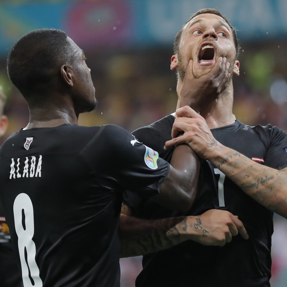 Austria's Marko Arnautovic, right, celebrates with Austria's David Alaba after scoring his side's third goal during the Euro 2020 soccer championship group C match between Austria and Northern Macedonia at the National Arena stadium in Bucharest, Romania, Sunday, June 13, 2021. (Robert Ghement/Pool