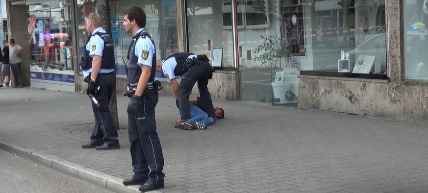 GERMANY OUT - In this grab taken from video, police officers arrest a man close to a machete, front right, after an attack in Reutilingen, Germany, Sunday, July 24, 2016. A Syrian man killed a woman with a machete and wounded two others Sunday outside a bus station in the southwestern German city of Reutlingen before being arrested. Police said there were no indications pointing to terrorism. (NONSTOP NEWS via AP)