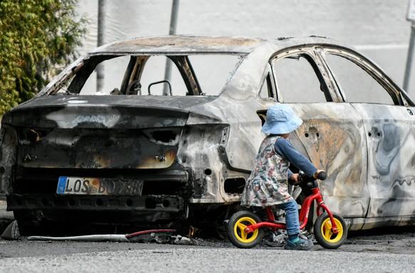 Ein Kind spielt am 7. Juli 2017 in Hamburg im Stadtteil Blankenese neben einem ausgebrannten Auto. Am 7. und 8. Juli kommen in der Hansestadt die Regierungschefs der fuehrenden Industrienationen zum G20-Gipfel zusammen. (KEYSTONE/DPA/Axel Heimken)