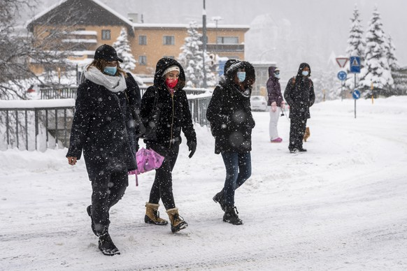 Ladies wearing protective masks walk on a snowy road, in St. Moritz, Switzerland, Saturday, December 5, 2020. Due to a heavy snowfall and strong wind, the FIS decided to cancel today's women's Super-G race of the FIS Alpine Ski World Cup. (KEYSTONE/Jean-Christophe Bott)