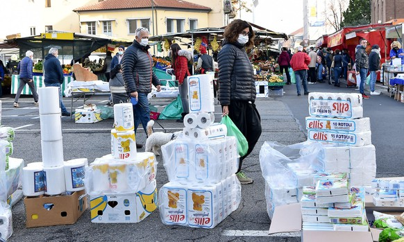 epa08804026 Clothing vendors at a street market protest against the recent coronavirus restrictions for businesses by showcasing toilet paper at the Crocetta market amid the ongoing coronavirus pandemic, in Turin, Italy, 07 November 2020.  EPA/Alessandro Di Marco