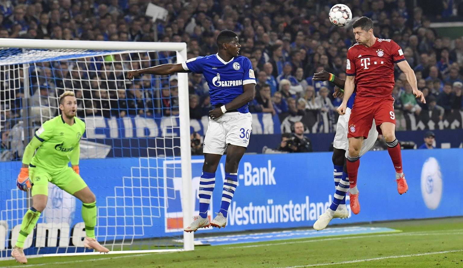 Bayern's Robert Lewandowski, right, heads the ball to Schalke goalkeeper Ralf Faehrmann, left, during the German Bundesliga soccer match between FC Schalke 04 and Bayern Munich in Gelsenkirchen, Germany, Saturday, Sept. 22, 2018. (AP Photo/Martin Meissner)