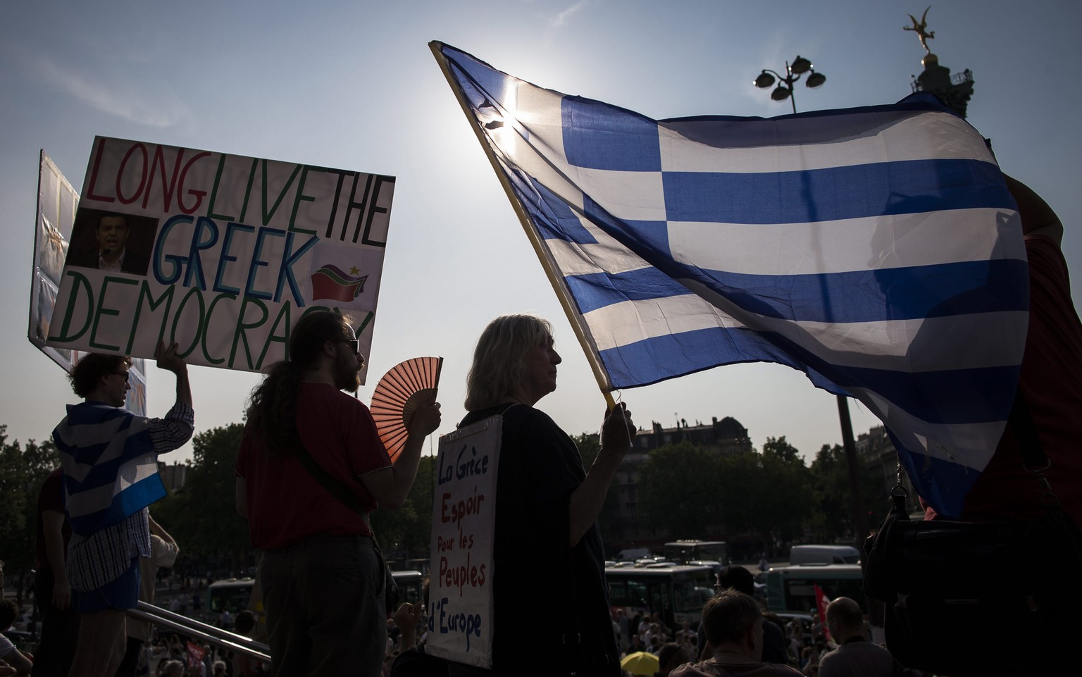 epaselect epa04828444 Protesters hold a Greek flag during a rally to support the Greek people, on Place de la Bastille, in Paris, France, 02 July 2015.  It would be 'extremely difficult' to keep Greece in the eurozone if the country votes 'no' in this weekend's referendum, Jeroen Dijsselbloem, the head of the Eurogroup of eurozone finance ministers, said on 02 July. On 05 July, Greek voters will be asked whether the country should accept reform proposals made by its creditors. Prime Minister Alexis Tsipras is telling people to reject the measures, arguing that a 'no' would give him a mandate for new bailout negotiations.  EPA/IAN LANGSDON