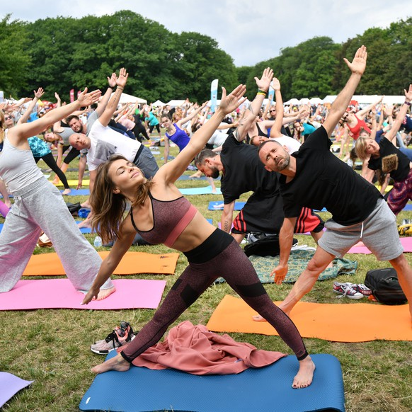 epa06050310 People attend a mass yoga session during the International Yoga Day on the Mokotow Field in Warsaw, Poland, 25 June 2017. The all day long Yoga day is celebrated with many attractions including Yoga exercises, lectures, discussions, and concerts. Participants could try natural and Indian food and buy eco products.  EPA/BARTLOMIEJ ZBOROWSKI POLAND OUT