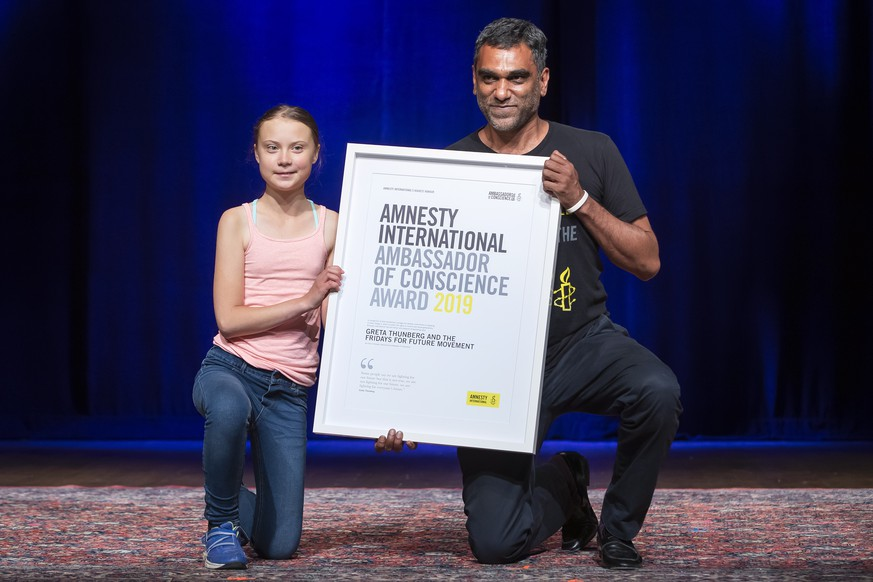 epa07847615 Swedish climate activist Greta Thunberg (L) poses with Amnesty International Secretary General Kumi Naidoo (R) after Thunberg was awarded Amnesty International's Ambassador of Conscience award at George Washington University in Washington, DC, USA, 16 September 2019. Thunberg is scheduled to attend the United Nations Climate Action Summit in New York City.  EPA/ERIK S. LESSER