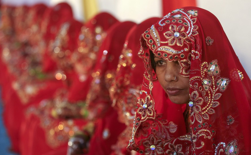 epa04064794 A Indian Muslim bride dressed in traditional marriage attire take part in a mass marriage ceremony in Mumbai, India, 09 February 2014. Around 28 couples got married during the ceremony which was organised by the Hazrat Shah Saqlain Academy of India, for the financially weaker strata of the society where couples tie the knot under the same roof at the same time.  EPA/DIVYAKANT SOLANKI