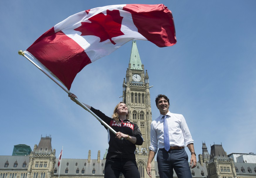 Canada's Prime Minister Justin Trudeau looks on as athlete Rosie MacLennan waves the Canadian flag after being named as the flag bearer for the upcoming Summer Olympics Thursday July 21, 2016 in Ottawa. (Adrian Wyld/The Canadian Press via AP)