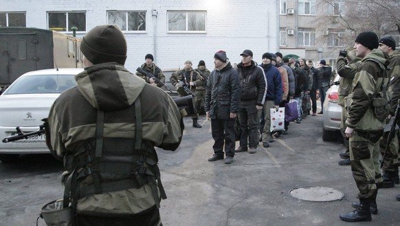 epaselect epa04540720 Ukrainian prisoners of war stand in line before their transportation to a place of exchange of pro-Russian rebels in Donetsk, Ukraine, 26 December 2014. The group, which includes Ukraine, Russia and the Organization for Security and Co-operation in Europe (OSCE), held a first round of talks with the pro-Russian separatists in the Belarusian capital on 24 December, during which they agreed on a prisoner swap. The exchange took place later on 26 December outside the rebel stronghold of Donetsk, when government forces released 225 separatist fighters and the separatists released 150 Ukrainian soldiers, Interfax reported.  EPA/ALEXANDER ERMOCHENKO