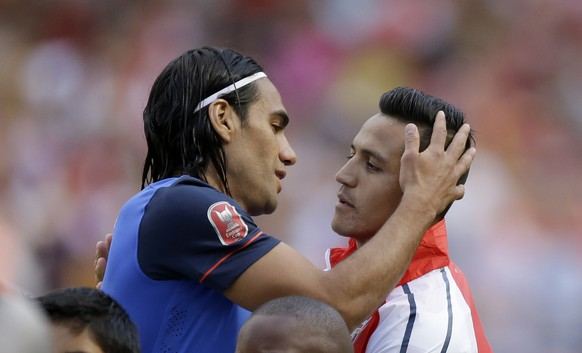 Arsenal's Alexis Sanchez, right, embraces AS Monaco's Radamel Falcao before the Emirates Cup soccer match between Arsenal and AS Monaco at Arsenal's Emirates Stadium in London, Sunday, Aug. 3, 2014.  (AP Photo/Matt Dunham)