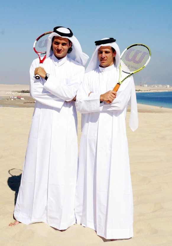 Swiss tennis number one seed Roger Federer, left, and Argentinean French Open winner Gaston Gaudio, right, pose while wearing Qatari traditional dress during a desert trip to the outskirts of Doha Sunday Jan. 2, 2005. Both players are in Doha to participate in the Qatar Open scheduled to start on Jan 3. (KEYSTONE/AP Photo)