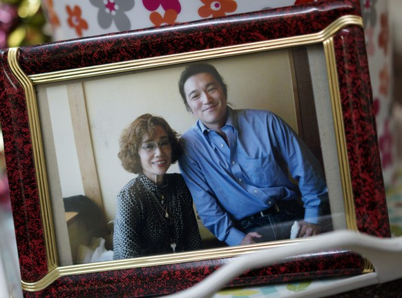 epa04593632 A framed photograph of Junko Ishido (L) and her son Kenji Goto (R), a Japanese journalist held by the Islamic State (IS) militant group, is seen displayed at her home in Tokyo, Japan, early 30 January 2015. Earlier in the day, an audio recording apparently of Japanese hostage Kenji Goto held by the Islamic State group, has given a new deadline of 29 January sunset for a prisoner swap between the militant group and Jordan. In the message, a man claiming to be Japanese journalist Kenji Goto says a Jordanian pilot held by the Islamic State will be killed if female militant Sajida al-Rishawi imprisoned in Jordan is not freed.  EPA/FRANCK ROBICHON