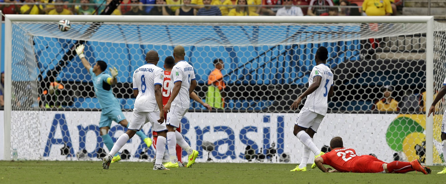 A shot from Switzerland's Xherdan Shaqiri, right, goes into the net for the opening goal during the group E World Cup soccer match between Honduras and Switzerland at the Arena da Amazonia in Manaus, Brazil, Wednesday, June 25, 2014. (AP Photo/Thanassis Stavrakis)