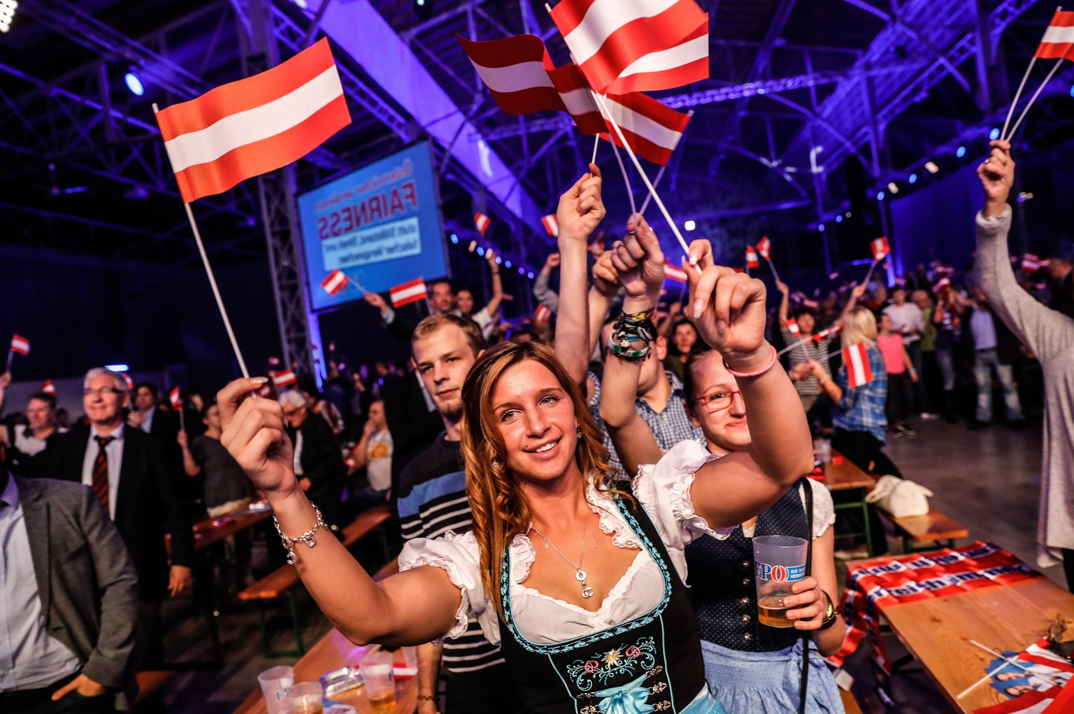 epa06267811 Supporters of the leader of the right-wing Austrian Freedom Party (FPOe) Heinz-Christian Strache (not pictured) waves small Austrian national flags as they watch a projection of the Austrian Federal Elections in Vienna, Austria, 15 October 2017. According to the Interior ministry more than six million people were eligible to vote in the elections for a new federal parliament, the Nationalrat, in Austria.  EPA/VALDRIN XHEMAJ
