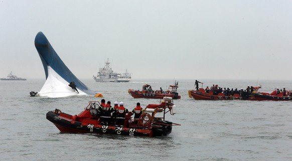 epa04168565 South Korean Coast Guard officers conduct a last-minute rescue operation around the passenger ferry Sewol sinking in waters off the southwestern coast of South Korea, 16 April 2014. The ferry, with 450 people on board, was reported sinking off the south-western coast of South Korea while en route from the port of Incheon, west of Seoul, to Jeju Island on 16 April. The passengers were mostly secondary school students on a field trip to Jeju island. The Coast Guard dispatched patrol boats and aircraft for rescue operations are under way. At least one dead has been reported.  EPA/YONHAP SOUTH KOREA OUT